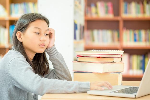 Uma menina está sentada para ler um livro na biblioteca