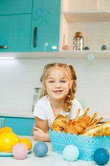 Uma menina está tomando café da manhã na cozinha com croissants e suco de laranja.