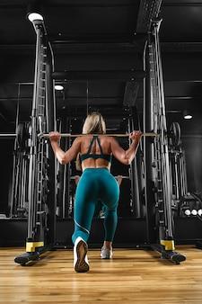 Uma menina está treinando as pernas na academia com um barbell