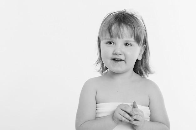 Uma menina faz careta contra um fundo branco.
