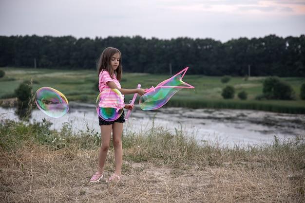 Uma menina faz grandes bolhas de sabão multicoloridas na natureza fora da cidade, descanso ativo.