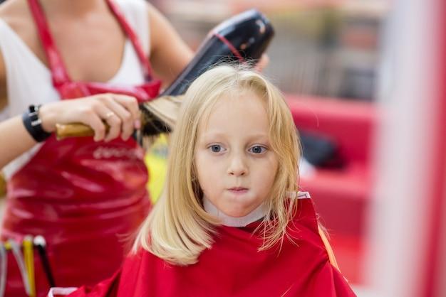 Uma menina faz um corte de cabelo.