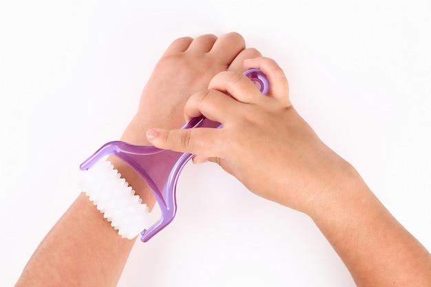Uma menina faz uma massagem de mão com massageador de mão