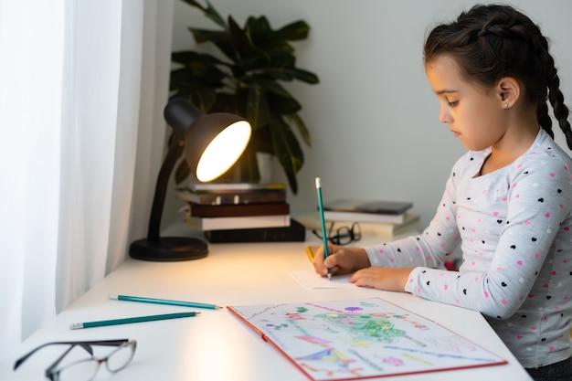 Uma menina fazendo lição de casa, escrevendo e lendo em casa