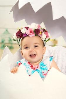 Uma menina feliz com flores na cabeça está sentada em um ovo decorativo. ovo de páscoa no cenário do estúdio.