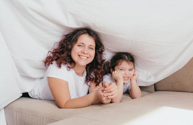 Uma menina feliz com uma gola alta abraça a mãe sob um lençol branco. uma mãe amorosa e carinhosa