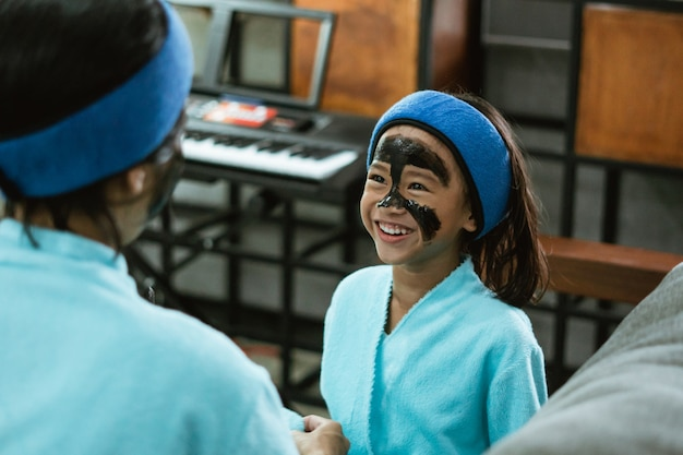 Uma menina feliz com uma máscara de argila preta na metade do rosto enquanto está sentada no sofá Foto Premium
