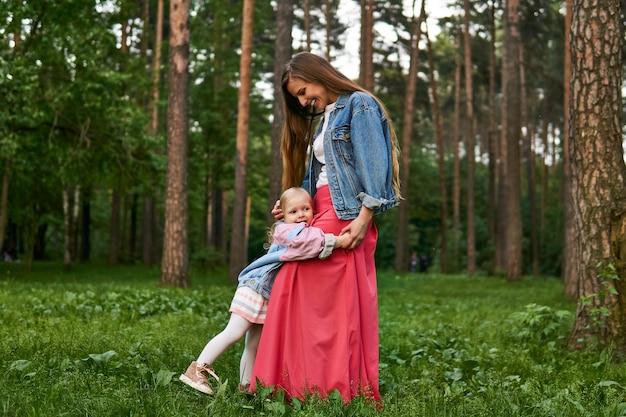 Uma menina feliz e rindo abraça a mãe em pé na grama do parque