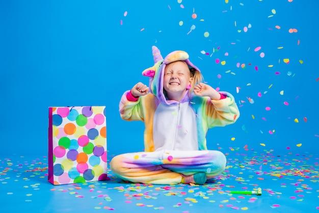 Uma menina feliz em um unicórnio kigurumi segura uma sacola de presente