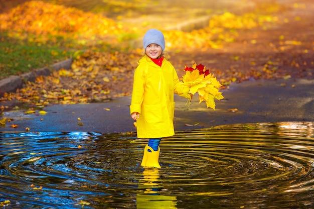 Uma menina feliz em uma capa de chuva amarela e botas de borracha em uma poça em uma caminhada de outono