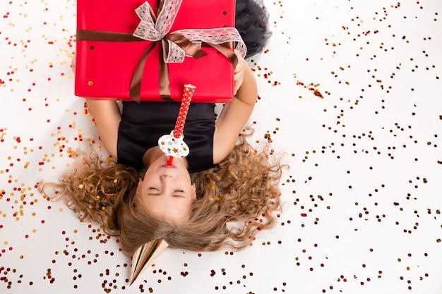 Uma menina feliz encontra-se em um fundo branco com uma caixa de presente e um boné de aniversário.