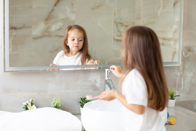 Uma menina feliz escova os dentes na frente de um espelho no banheiro. rotina matinal. higiene. foto de alta qualidade