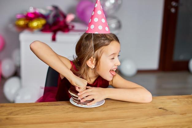 Uma menina feliz está usando um chapéu de aniversário e comendo um bolo de aniversário