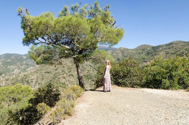 Uma menina fica ao lado de um pinheiro nas montanhas de chipre