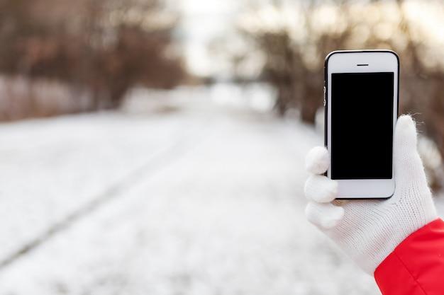 Uma menina fica no quadril um telefone celular