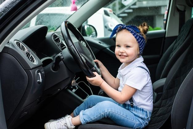Uma menina finge dirigir um carro. conceito de educação infantil, aprendizagem, dirigir um carro, engraçado, feliz, brincar, felicidade, seguro automóvel