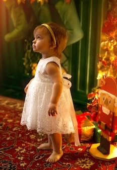 Uma menina fofa de um ano de idade está de pé ao lado da lareira com meias de natal