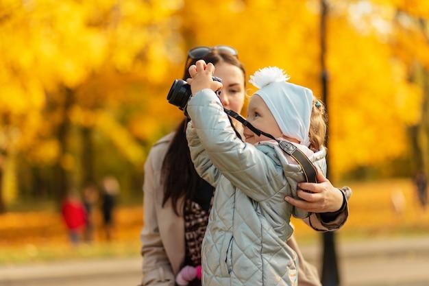 Uma menina fotógrafa com uma câmera tira uma foto no outono parque amarelo ao ar livre