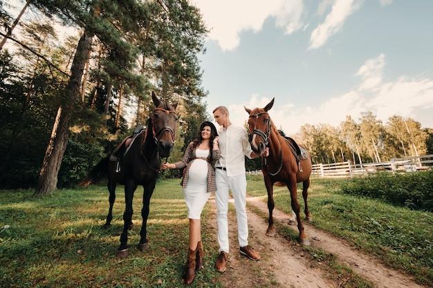 Uma menina grávida com um chapéu e o marido com roupas brancas estão ao lado de cavalos na floresta na natureza. mulher grávida elegante com um homem com cavalos. família.