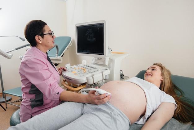 Uma menina grávida recebe um ultra-som de seu abdômen na clínica. exame médico