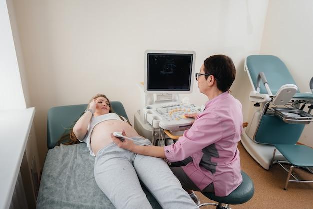 Uma menina grávida recebe um ultra-som de seu abdômen na clínica. exame médico.