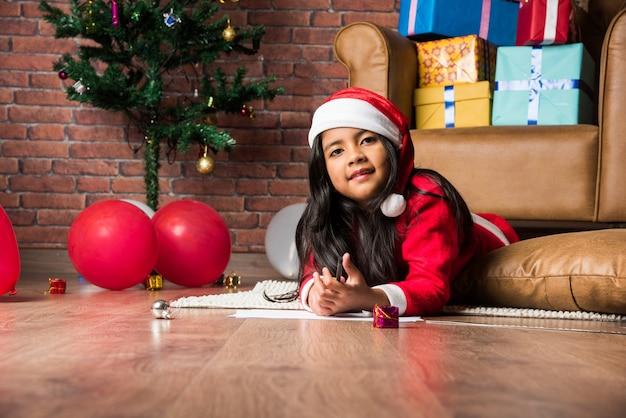 Uma menina indiana asiática escreve uma carta para o papai noel no natal enquanto está sentada no chão em casa com os presentes no fundo