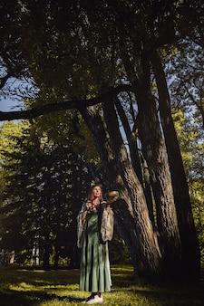 Uma menina iogue parada na floresta verde matinal com uma tigela tibetana cantante nas mãos