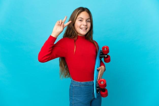 Uma menina isolada em um azul com um skate e uma expressão feliz