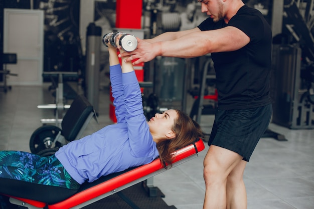Uma menina jovem e bonita com o namorado dela treinando em um ginásio