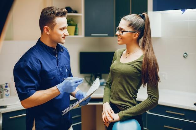 Uma menina jovem e bonita consulta com um dentista no consultório do dentista