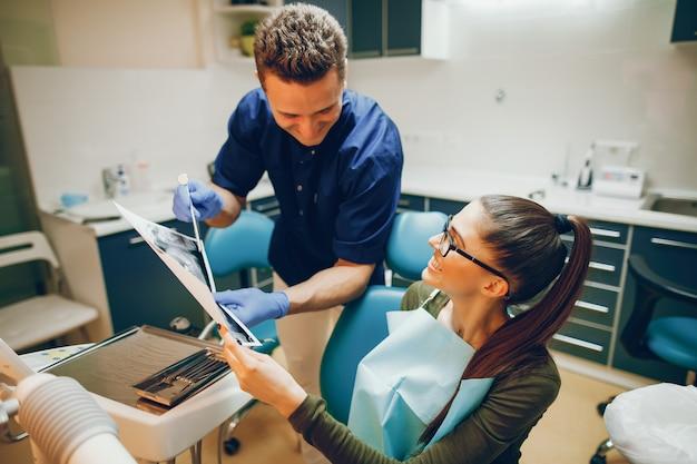 Uma menina jovem e bonita trata seus dentes com um dentista