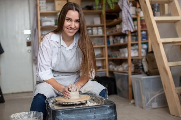 Uma menina jovem oleiro, sentado em uma oficina de cerâmica atrás de uma roda de oleiro