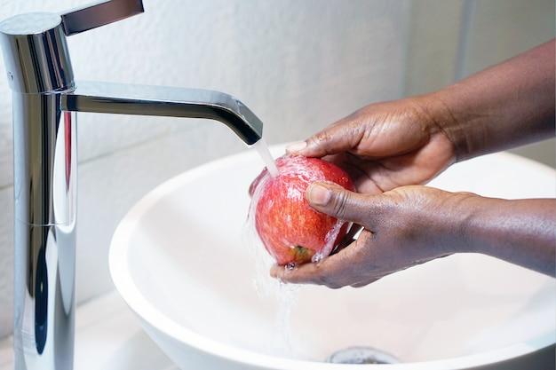 Uma menina lava uma maçã debaixo da torneira
