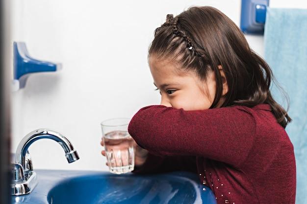 Uma menina limpando o rosto com o braço depois de lavar os dentes