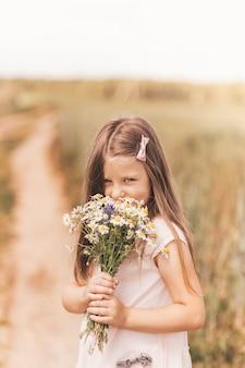 Uma menina linda com um buquê de margaridas em um campo de trigo