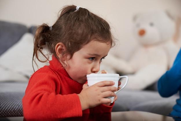 Uma menina linda criança vestindo um suéter vermelho, bebendo um delicioso chocolate quente com marshmellows.