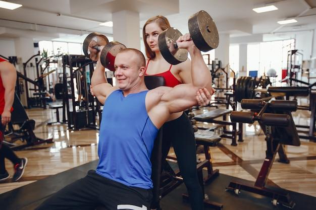 Uma menina linda e atlética sportswear treinando na academia com o amigo
