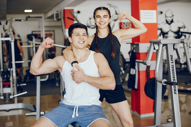 Uma menina linda e atlética sportswear treinando no ginásio com o namorado