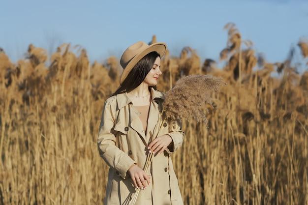 Uma menina linda e delicada com os olhos fechados, vestindo uma capa impermeável bege e um chapéu segurando um buquê de capim-dos-pampas