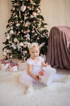 Uma menina linda em um vestido branco festivo sentada em um cobertor perto da árvore de natal com um presente