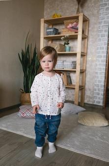 Uma menina linda em um vestido marrom olha para você enquanto está de pé na sala. bebê feliz