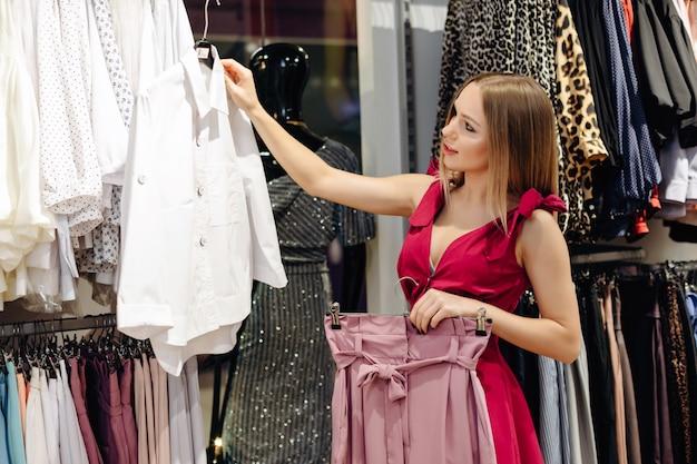 Uma menina linda em uma loja de roupas femininas escolhe uma blusa branca e uma saia rosa de uma nova coleção.