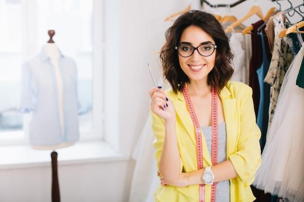 Uma menina linda morena com um vestido cinza e uma jaqueta amarela está de pé perto de roupas no estúdio. ela está sorrindo para a câmera.