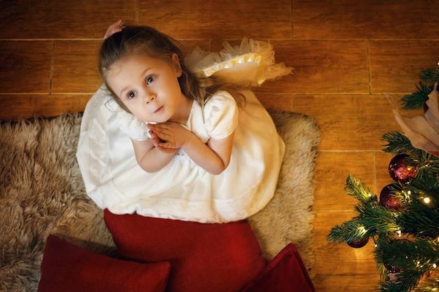 Uma menina loira anjo de 3 a 5 anos sentada no tapete perto da árvore de ano novo
