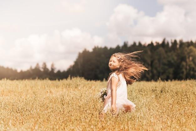 Uma menina loira caminha por um campo dourado no verão. conceito de pureza, crescimento, felicidade