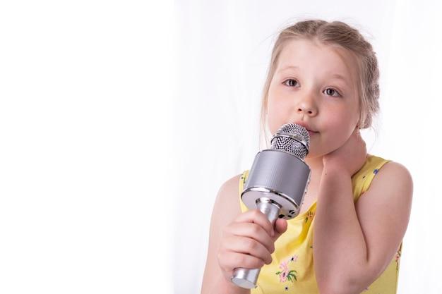Uma menina loira canta uma música em um microfone em suas mãos