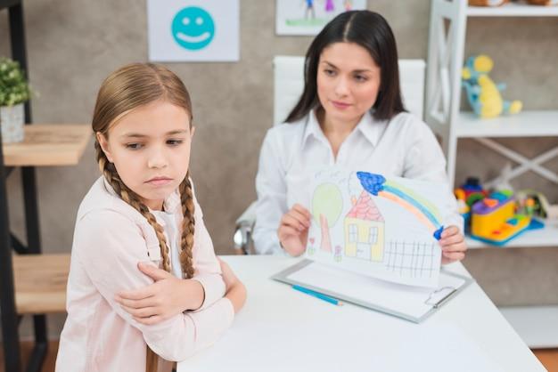 Uma menina loira com raiva não olhando para o papel de desenho mostrado por seu psicólogo