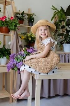 Uma menina loira com um buquê de flores lilás está sentada em uma cadeira de madeira na sala