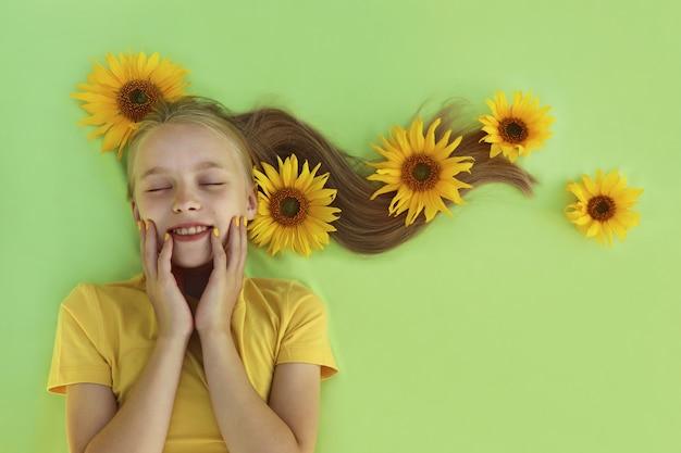 Uma menina loira com uma manicure de bebê amarelo e girassóis no cabelo