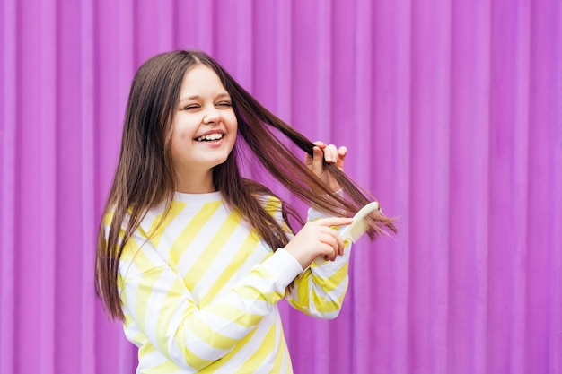 Uma menina loira de cabelo comprido e alegre penteia o cabelo com um pente e ri descuidadamente.